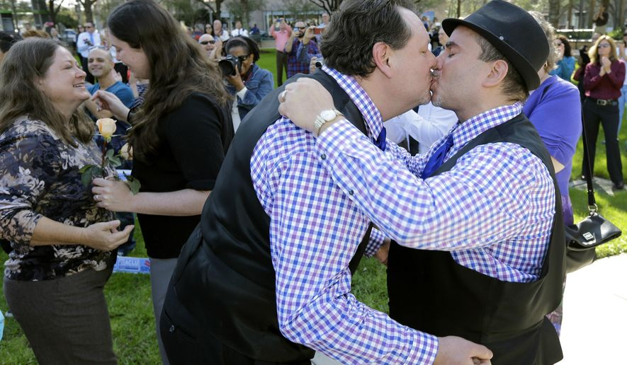 Alberto Molina-Coats, right, kisses his new spouse Glenn Molina-Coats after a mass same-sex wedding near the Hillsborough County Courthouse Tuesday, Jan. 6, 2015, in Tampa, Fla.  Clerk of the Circuit Court, Pat Frank, married the couple after U.S. District Judge Robert L. Hinkle's ruling that Florida's same-sex marriage ban is unconstitutional took effect early Tuesday in all 67 counties.(AP Photo/Chris O'Meara)