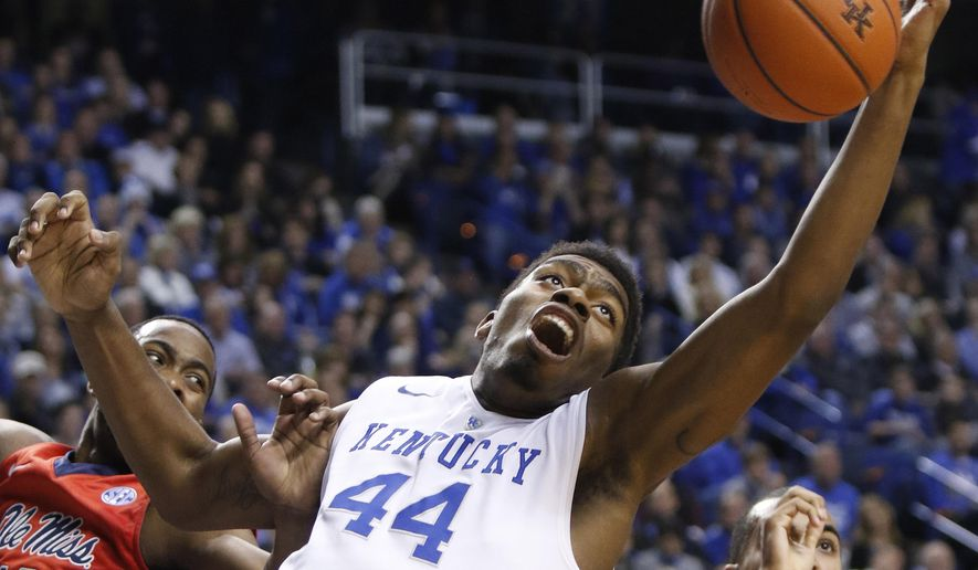 Kentucky's Dakari Johnson (44) reaches for a rebound next to Mississippi's LaDarius White during the first half of an NCAA college basketball game in Lexington, Ky., Tuesday, Jan. 6, 2015. (AP Photo/James Crisp)