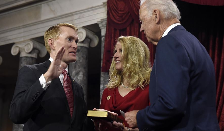 Vice President Joe Biden administers the Senate oath to Sen. James Lankford R-Okla. during a ceremonial re-enactment swearing-in ceremony, Tuesday, Jan. 6, 2015, in the Old Senate Chamber on Capitol Hill in Washington. Lankford's wife Cindy is at center. (AP Photo/Susan Walsh)