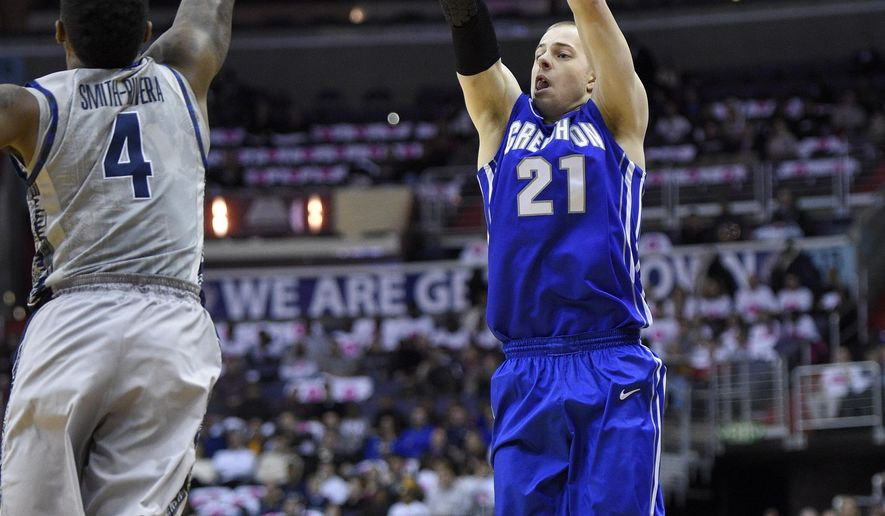 Creighton guard Isaiah Zierden (21) puts up a shot against Georgetown guard D'Vauntes Smith-Rivera (4) during the first half of an NCAA college basketball game, Saturday, Jan. 3, 2015, in Washington. (AP Photo/Nick Wass)