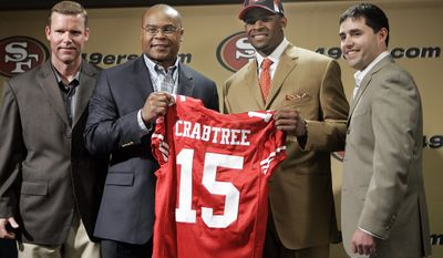 Michael Crabtree, center right, the San Francisco 49ers 2009 NFL football first round draft pick, holds up his new jersey number as he smiles with head coach Mike Singletary, center left, 49ers general manager Scot McCloughan, left, and 49ers president Jed York, right, during a news conference at 49ers headquarters in Santa Clara, Calif., Sunday, April 26, 2009. Crabtree was a wide receiver from Texas Tech. (AP Photo/Paul Sakuma)