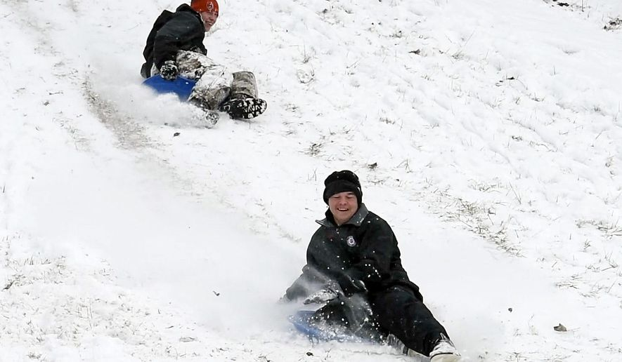 Michael Rinehart, left, and Eric Kessler use their snow day away from Middletown High School to sled at the campus of Miami University in Middletown, Ohio on Tuesday, Jan. 6, 2015. The National Weather Service says temperatures were expected to reach single digits with wind chills below zero in most of Ohio overnight Tuesday into Wednesday. (AP Photo/The Dayton Daily News, Nick Graham)