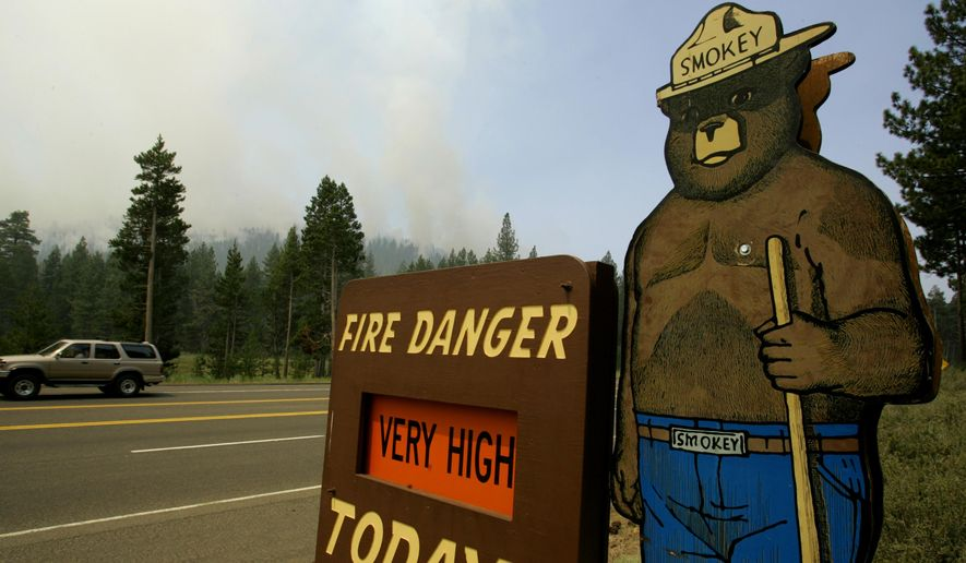 This June 26, 2007 file photo shows a sign depicting U.S. Forest mascot Smokey Bear on a fire danger sign in South Lake Tahoe, Calif., as smoke from a wildfire rises behind it. (AP Photo/Ben Margot, File)