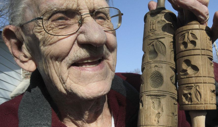 In this Dec. 17, 2014 photo, longtime woodcarver Don Lougeay, of Belleville, Ill., holds up two very old rolling pins that make special impressions in cookie dough as it is being rolled. (AP Photo/Belleville News-Democrat, Tim Vizer)