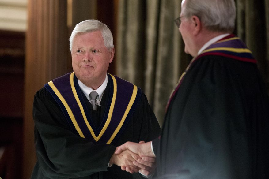 Supreme Court Chief Justice Thomas Saylor, left, shakes hands with outgoing Supreme Court Chief Justice Ron Castille during a ceremony inducting him as Pennsylvania's 56th chief justice of the Supreme Court, Tuesday, Jan. 6, 2015, in the Supreme Court's courtroom at the state Capitol in Harrisburg, Pa. Saylor succeed Castille, who reached the mandatory retirement age of 70 last year. (AP Photo/Matt Rourke)