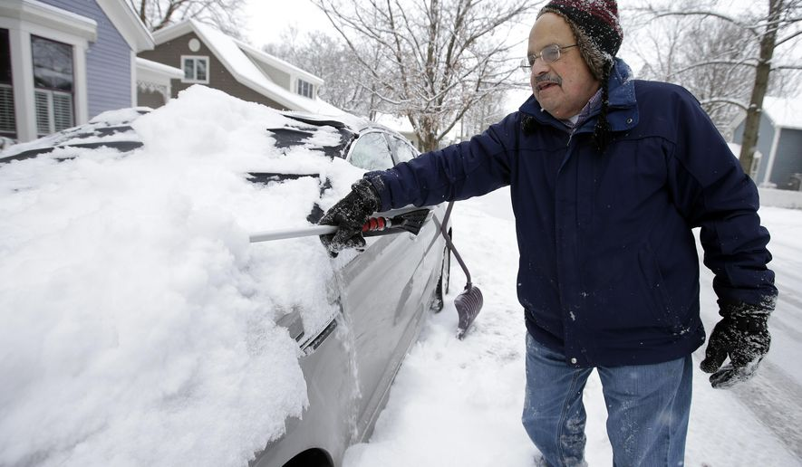 Mike Mindel scrapes snow off his car, Tuesday, Jan. 6, 2015, in Zionsville, Ind. Temperatures in central and northern Indiana are predicted to drop into the lower teens Tuesday and reach no higher than 5 degrees Wednesday. (AP Photo/Darron Cummings)