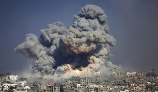 In this July 29, 2014, file photo, smoke and fire from an Israeli strike rise over Gaza City. A fierce debate is raging within Israel's military over the extent to which soldiers should be held legally accountable for their actions during last year's Gaza war, with commanders increasingly at odds with military lawyers. (AP Photo/Hatem Moussa, File)