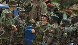 U.S. Army special forces Master Sergeant Eric, center, who would only give his first name in accordance with special forces security guidelines, speaks with troops from the Central African Republic and Uganda, in Obo, Central African Republic, where U.S. special forces have paired up with local troops and Ugandan soldiers to seek out Joseph Kony's Lord's Resistance Army (LRA), April 29, 2012. (Associated Press) ** FILE **