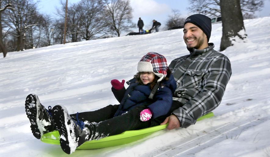 Jaime Rodas and his daughter, Aria Rodas 3 enjoy an afternoon of sledding on Tuesday Jan. 6, 2015 on a hill in Jim Barnett Park in Winchester, Vvaa. (AP Photo/The Winchester Star, Ginger Perry)