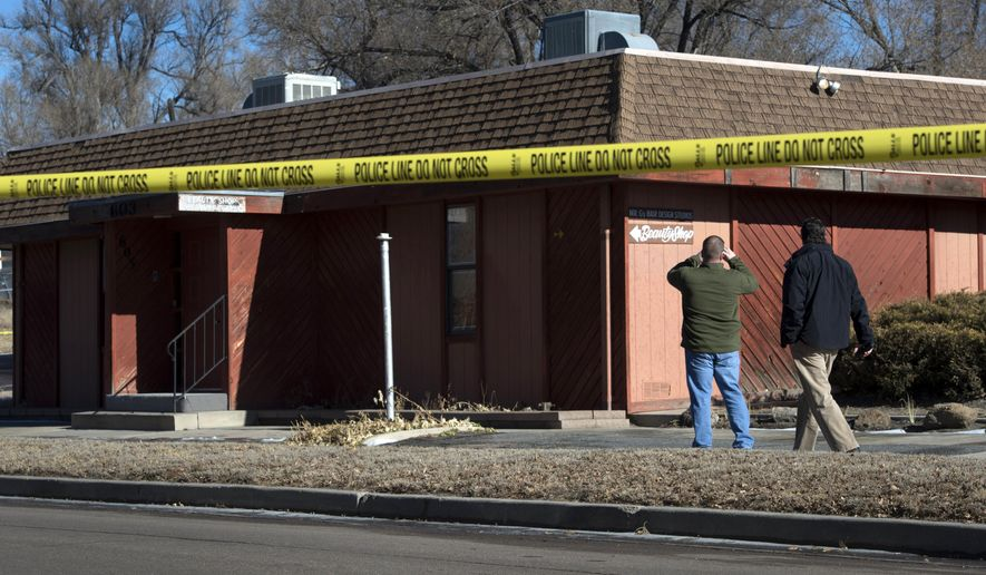 Colorado Springs police officers investigate the scene of an explosion Tuesday, Jan. 6, 2015, at a building in Colorado Springs, Colo. Authorities are investigating whether a homemade explosive set off outside the building that houses a barber shop and the Colorado Springs chapter of the NAACP was aimed at the nation's oldest civil rights organization. (AP Photo/The Colorado Springs Gazette, Christian Murdock ) MAGS OUT