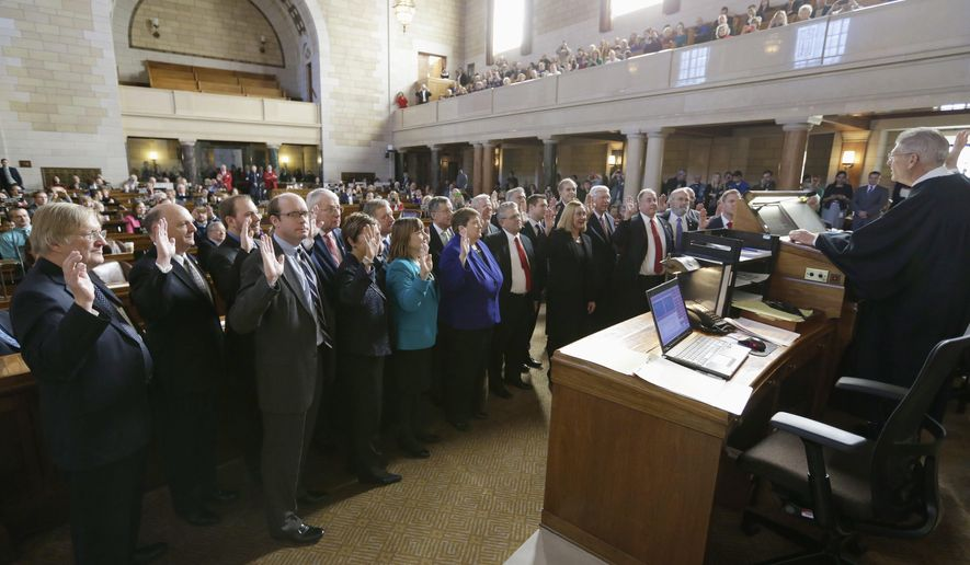 Nebraska Chief Justice Mike Heavican, right, swears in 18 new state senators on the first day of the legislative session in Lincoln, Neb., Wednesday, Jan. 7, 2015. The Nebraska Legislature kicked off its 2015 session with an expected focus on property taxes and the state's scandal-plagued prison system. (AP Photo/Nati Harnik)