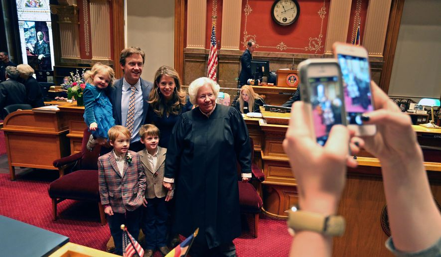 Colorado State Sen. Mike Johnston, second from left, stands with his wife and children as they pose for a snapshot with  state Supreme Court Chief Justice Nancy Rice, during the opening session of the 2015 Colorado Legislature, at the Capitol, in Denver, Wednesday Jan. 7, 2015. Johnston's family are, left to right, Ava, 3, Seamus, 7, Emmet, 7, and his wife Courtney. (AP Photo/Brennan Linsley)