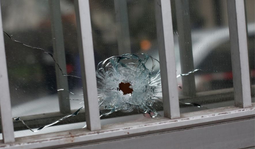 """A bullet impact is seen in a window of a building next to the French satirical newspaper Charlie Hebdo's office, in Paris, Wednesday. Masked gunmen shouting """"Allahu akbar!"""" stormed the Paris offices of a satirical newspaper Wednesday, killing at least 12 people, including the paper's editor, before escaping in a getaway car. (Associated press)"""