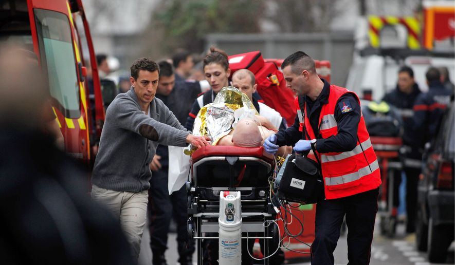 An injured person is whisked from the scene of deadly shootings at the offices of Charlie Hebdo, a Paris weekly. (Associated Press)