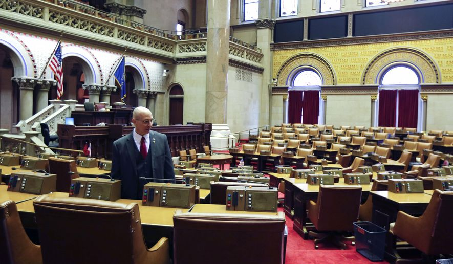 Assemblyman Dean Murray R-East Patchogue, stands near his desk in the Assembly Chamber at the state Capitol on Tuesday, Jan. 6, 2015, in Albany, N.Y. Murray won back his old Assembly seat and will be sworn in this afternoon. The 2015 legislative session begins on Wednesday. (AP Photo/Mike Groll)
