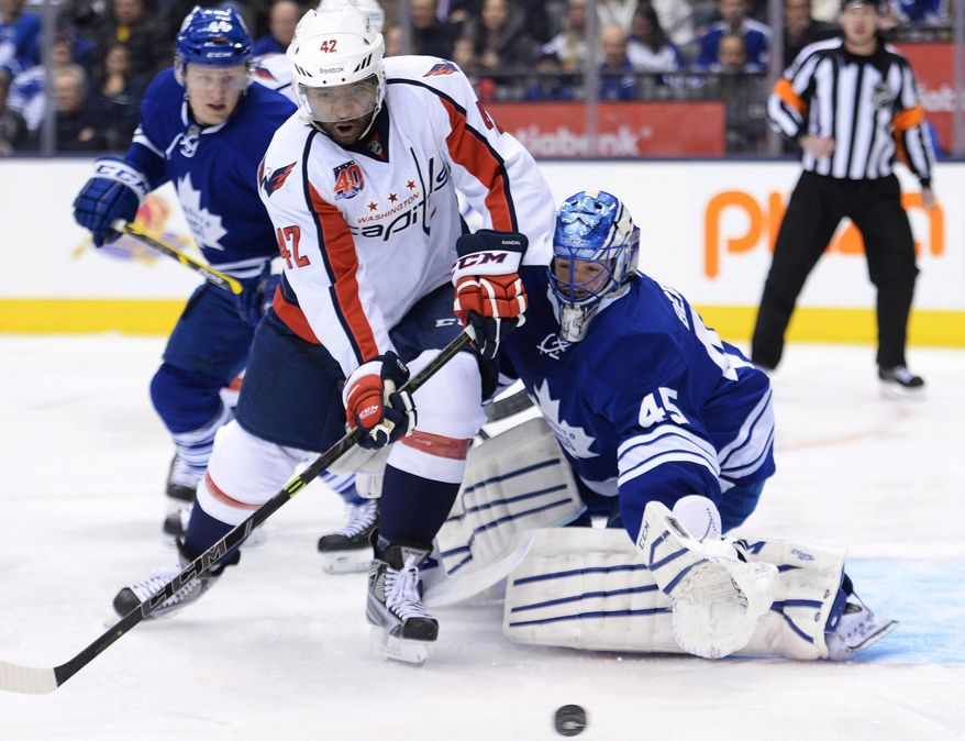 Toronto Maple Leafs goalie Jonathan Bernier (45) stops Washington Capitals forward Michael Latta (46) during the first period of an NHL hockey game, Wednesday, Jan. 7, 2015 in Toronto. (AP Photo/The Canadian Press, Nathan Denette)