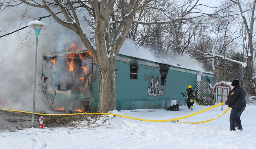 Firefighters battle a mobile home fire, Wednesday, Jan. 7, 2015, in Three Rivers, Mich. Authorities say two young children died in the morning fire, and their mother was taken to a hospital for treatment. (AP Photo/The Commercial-News, Elena Hines)