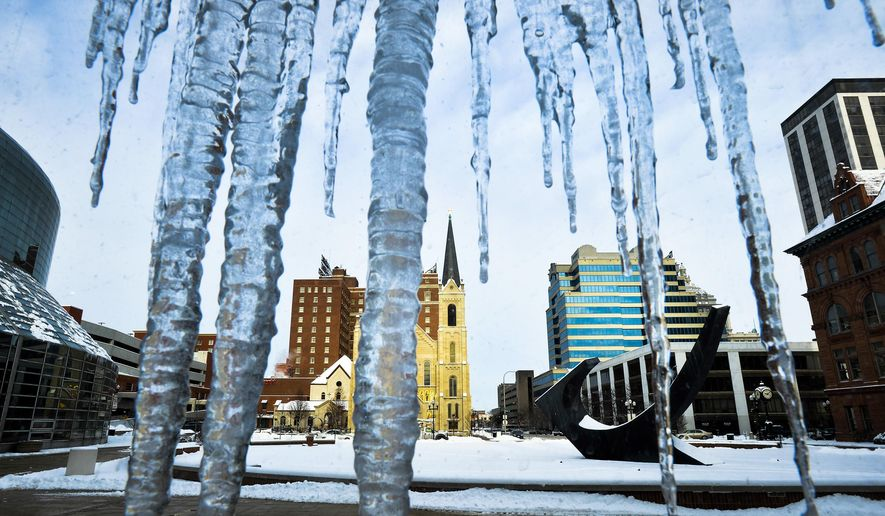 The skyline of the city of Peoria, Ill., is viewed through the glass atrium of the Peoria Civic Center on Tuesday, Jan. 6, 2015, as melting snow became icicles after from the first significant winter snowfall on Monday evening. (AP Photo/Journal Star, Ron Johnson)