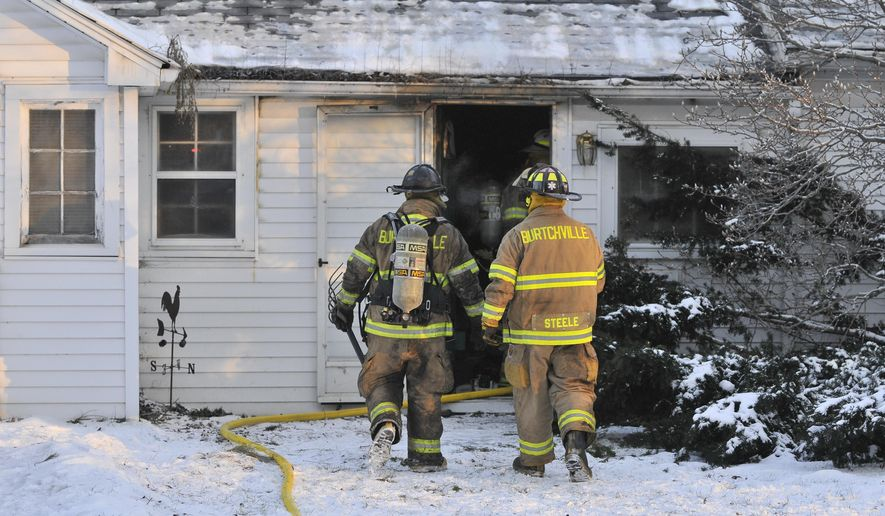 Two Burtchville Township firefighters walk back into the house as they look for hot spots in the attic of the house fire where Thomas Tsafaroff, 66, was found dead, Tuesday morning, Jan. 6, 2015, in Burtchville Township, Mich, about 10 miles north of Port Huron.  Michigan State Police Detective Sgt. Daniel Drake told the The Port Huron Times Herald that the investigation into the fire and Tsafaroff's death are ongoing, but do not appear suspicious. (AP Photo/The Port Huron Times Herald, Mark R. Rummel)  NO SALES