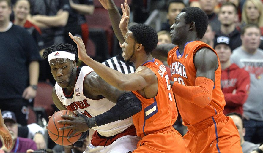 Louisville's Montrezl Harrell, left, attempts to work the ball inside through the defense of Clemson's Jaron Blossomgame, center, and Sidy Djitte during the first half of their NCAA basketball game, Wednesday, Jan. 7, 2015, in Louisville, Ky. (AP Photo/Timothy D. Easley)