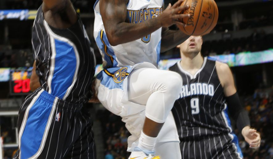 Denver Nuggets guard Ty Lawson, front, drives the lane for a shot between Orlando Magic guard Ben Gordon, back left, and center Nikola Vucevic, of Montenegro, in the first quarter of an NBA basketball game Wednesday, Jan. 7, 2015, in Denver. (AP Photo/David Zalubowski)