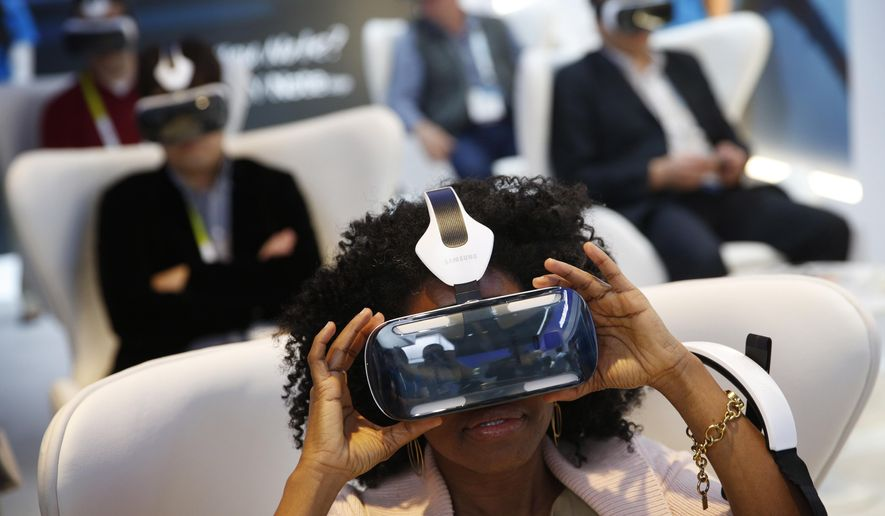 Yasmin Moorman looks into the Galaxy Gear VR headset at the Samsung booth during the International CES, Tuesday, Jan. 6, 2015, in Las Vegas. (AP Photo/John Locher)
