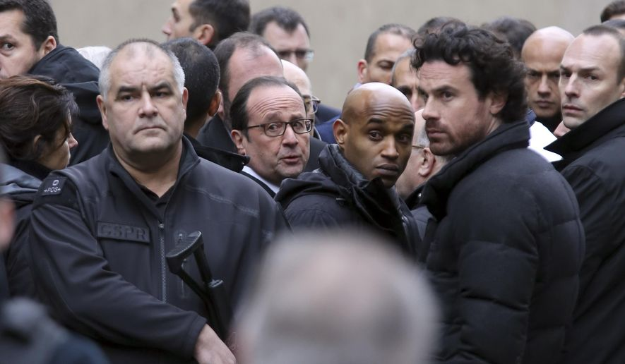 French President Francois Hollande, center, flanked with security forces arrives outside the French satirical newspaper Charlie Hebdo's office, in Paris, Wednesday, Jan. 7, 2015. Masked gunmen stormed the offices of a French satirical newspaper Wednesday, killing at least 11 people before escaping, police and a witness said. The weekly has previously drawn condemnation from Muslims. (AP Photo/Remy De La Mauviniere)