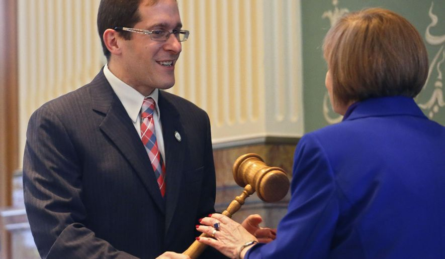 Outgoing Democratic Colorado House Speaker Rep. Mark Ferrandino, left, hands the gavel to incoming Democratic Colorado House Speaker Rep. Dickey Lee Hullinghorst, during the opening session of the 2015 Colorado Legislature, at the Capitol, in Denver, Wednesday Jan. 7, 2015. While Republicans have control of the Senate for the first time in a decade, Democrats are still in control of the House. AP Photo/Brennan Linsley)
