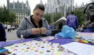 Carmay Albano cuts a paper star for the Center for Victims quilt, an event to raise awareness of domestic violence in Pittsburgh. (AP Photo/Keith Srakocic)