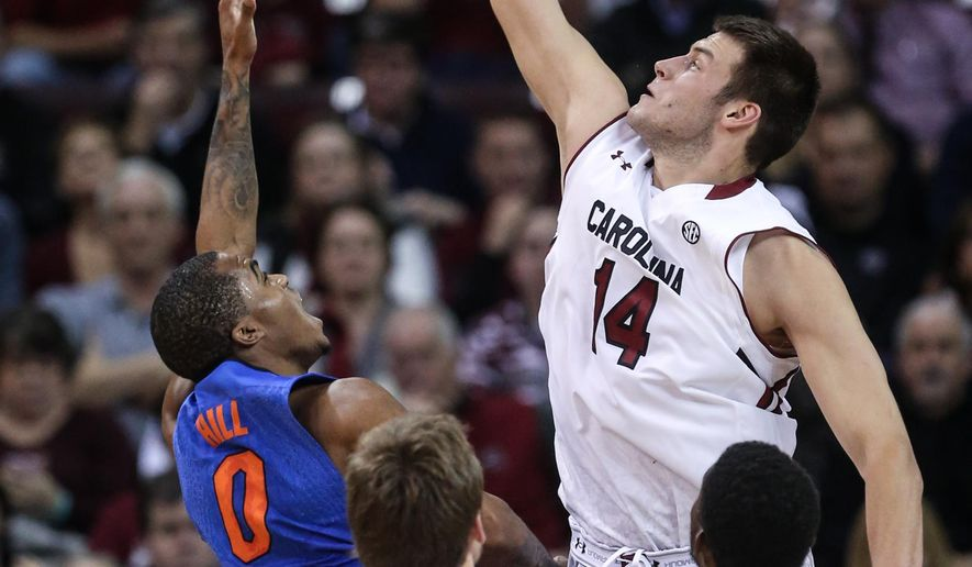 South Carolina forward Laimonas Chatkevicius (14) blocks a shot by Florida guard Kasey Hill (0) during the first half of an NCAA college basketball game Wednesday, Ja. 7, 2015, in Columbia, S.C. (AP Photo/The State, Tracy Glantz)