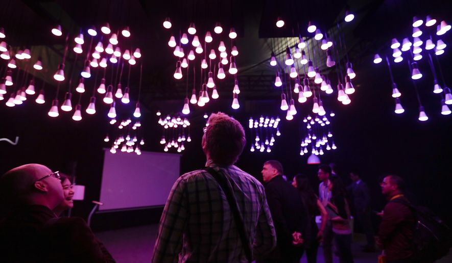 Attendees look at a display made with Playbulb Bluetooth-enabled LED color light bulbs at the MiPow booth at the International CES Tuesday, Jan. 6, 2015, in Las Vegas. (AP Photo/Jae C. Hong)