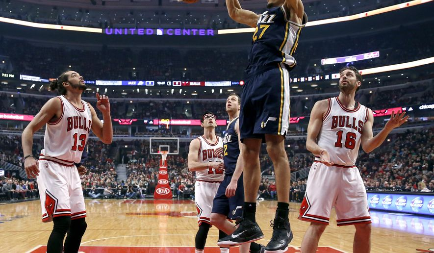 Utah Jazz center Rudy Gobert (27) dunks the ball as Chicago Bulls Joakim Noah (13), Kirk Hinrich (12)  Jazz Joe Ingles (2), and Bulls Pau Gasol watch, during the first half of an NBA basketball game Wednesday, Jan. 7, 2015, in Chicago. (AP Photo/Charles Rex Arbogast)