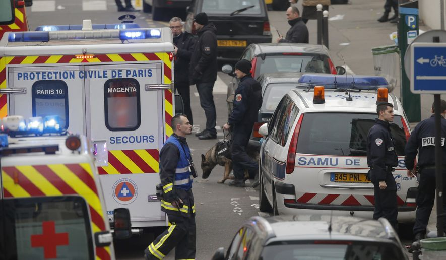 Police and rescue workers patrol the street outside the French satirical newspaper Charlie Hebdo's office, in Paris, Wednesday, Jan. 7, 2015. Masked gunmen stormed the offices of a French satirical newspaper Wednesday, killing at least 11 people before escaping, police and a witness said. The weekly has previously drawn condemnation from Muslims. (AP Photo/Francois Mori)