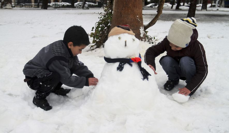 Children make a snowman in Damascus, Syria, Wednesday, Jan. 7, 2015. (AP Photo)