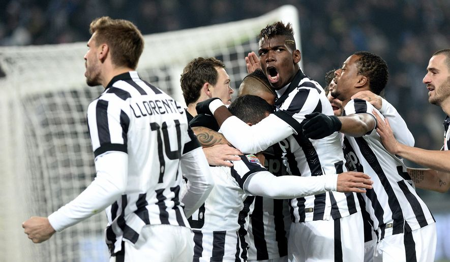 Juventus' players celebrates Carlos Tevez after he scored during a Serie A soccer match between Juventus and  Inter Milan at the Juventus stadium, in Turin, Italy, Tuesday, Jan. 6, 2015. (AP Photo/ Massimo Pinca)