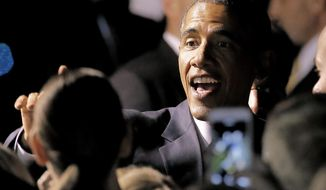 President Barack Obama greets supporters after arriving at Sky Harbor International Airport, Wednesday, Jan. 7, 2015, in Phoenix. The President will overnight in Arizona before speaking at Central High School in Phoenix on Thursday. (AP Photo/Matt York)