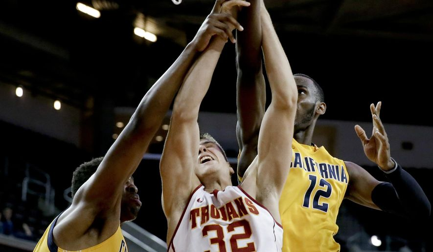 Southern California forward Nikola Jovanovic, middle, and California forward Roger Moute a Bidias, right, and center Kingsley Okoroh reach for a rebound during the first half of an NCAA college basketball game in Los Angeles, Wednesday, Jan. 7, 2015. (AP Photo/Chris Carlson)