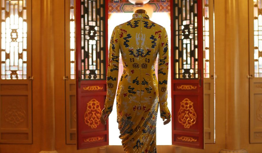 "In this image released by The Costume Institute at The Metropolitan Museum of Art, a gown is displayed in Beijing, China. The spring exhibition at the Metropolitan Museum of Art's Costume Institute will be ""China: Through the Looking Glass,"" the museum announced Thursday, Jan. 8, 2015, at a media briefing in Beijing. The show will run from May 7 to Aug. 16 in the Met's Chinese Galleries and in the Anna Wintour Costume Center in New York. It will feature more than 130 fashions juxtaposed with Chinese art pieces in jade, lacquer and porcelain. The Costume Institute's star-studded annual benefit May 4 will celebrate the exhibition's opening. (AP Photo/The Costume Institute at The Metropolitan Museum of Art)"