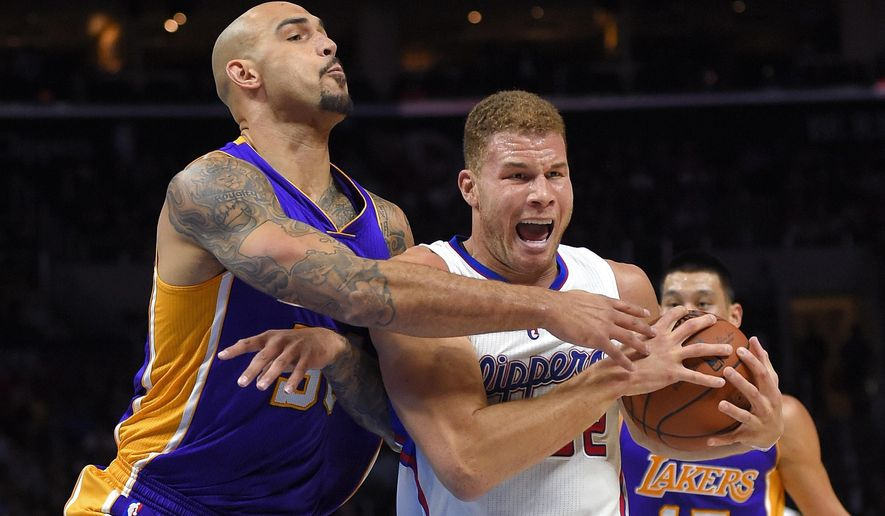 Los Angeles Lakers center Robert Sacre, left, reaches for the ball held by Los Angeles Clippers forward Blake Griffin during the first half of an NBA basketball game, Wednesday, Jan. 7, 2015, in Los Angeles. (AP Photo/Mark J. Terrill)