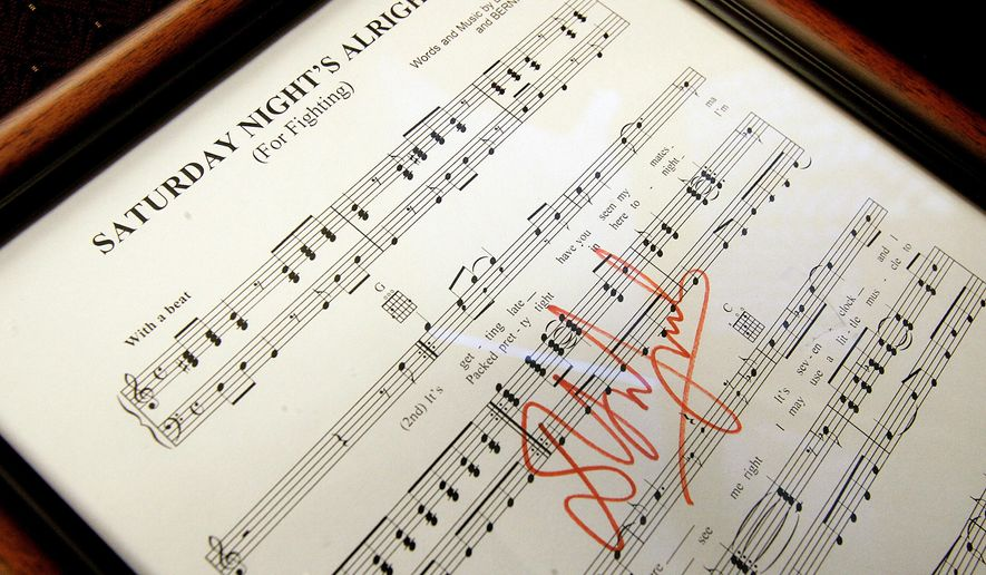 """This Wednesday, Jan. 7, 2015 photo shows autographed sheet music for Elton John's """"Saturday Nights' Alright"""" song that was on a shelf and not on the wall when Podiatrist Jeffery H. Katz's office was broken into and robbed over the weekend in Corona, Calif. Katz estimates the collection he collected over 40 years is worth a quarter of a million dollars. It includes album covers signed by all four Beatles, Led Zeppelin, the Eagles, Bob Dylan and others. (AP Photo/The Press-Enterprise, Terry Pierson)"""