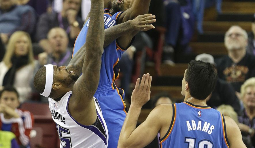 Sacramento Kings center DeMarcus Cousins, left, goes to the basket against Oklahoma City Thunder forward Serge Ibaka, center, of the Republic of Congo, as Thunder center Steven Adams, of New Zealand, right, looks on during the first quarter of an NBA basketball game in Sacramento, Calif., Wednesday, Jan. 7,  2015. (AP Photo/Rich Pedroncelli)