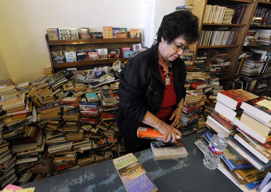Martha Jarred cleans a paperback book cover with furniture polish Dec. 12, 2014, at Henderson Book Store in Haskell. Jarred tries to clean each book that comes in the used book store. (AP Photo/The Abilene Reporter-News, Ronald W. Erdrich)