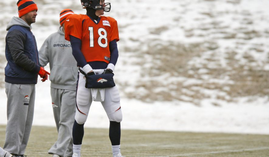 Denver Broncos quarterback Peyton Manning tries to keep his hands warm in a pouch during practice for the team's NFL football divisional playoff game against the Indianapolis Colts Wednesday, Jan. 7, 2015, in Englewood, Colo. (AP Photo/David Zalubowski)