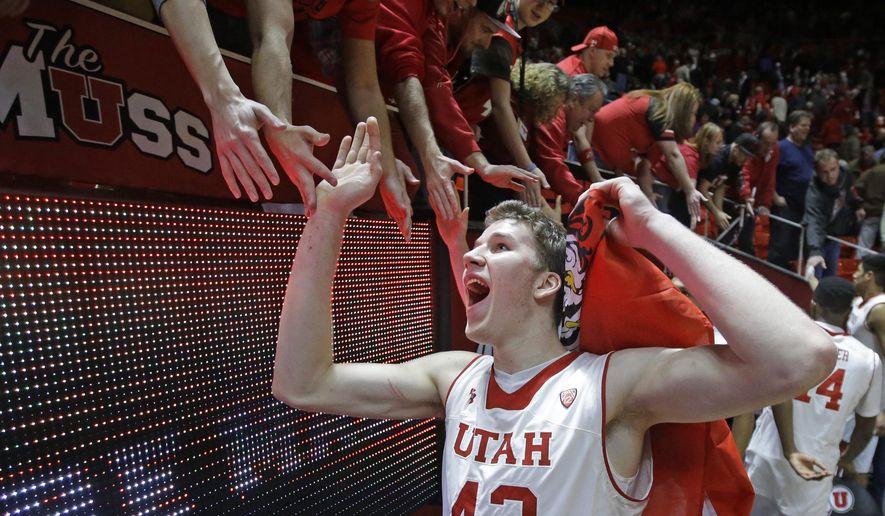 Utah forward Jakob Poeltl (42) celebrates with fans following an NCAA college basketball game against Colorado, Wednesday, Jan. 7, 2015, in Salt Lake City. Utah won 74-49. (AP Photo/Rick Bowmer)