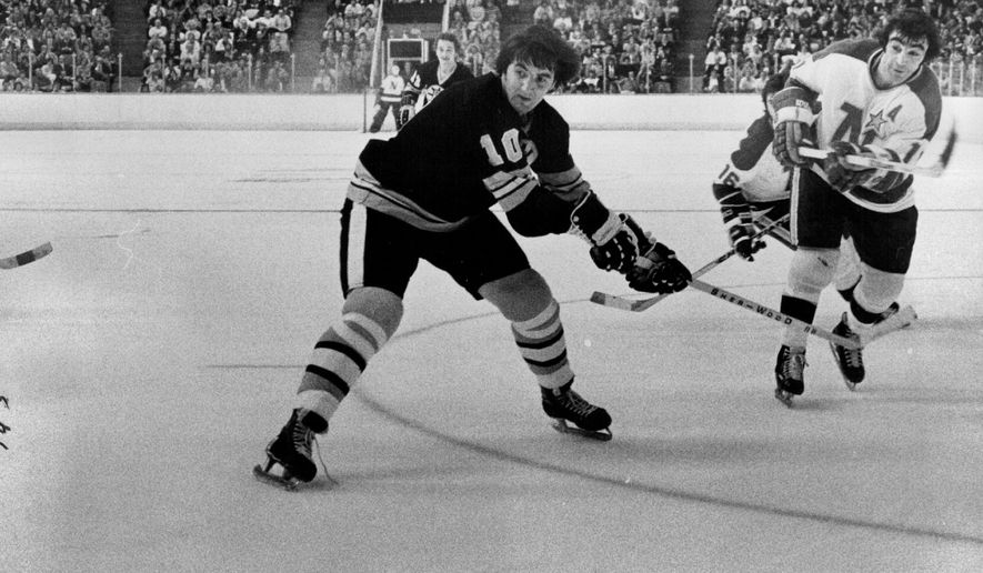 In this Oct. 31, 1974, photo, Minnesota  North Stars J.P. Parise, far right,  scores as Boston Bruins Carol Vadnais, center, looks on in Bloomington, Minn. Parise has died from lung cancer. He was 73. The Minnesota Wild said Thursday he died Wednesday night, Jan. 7, 2015,  at his home in the Minneapolis suburb of Prior Lake. Son and Wild star Zach Parise informed the team of his father's death. (AP Photo/The Star Tribune, Roger Nystrom)  MANDATORY CREDIT; ST. PAUL PIONEER PRESS OUT; MAGS OUT; TWIN CITIES LOCAL TELEVISION OUT