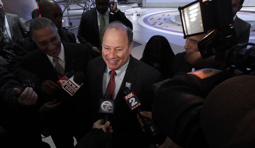 Detroit Mayor Mike Duggan speaks on the floor of the upcoming North American International Auto Show in Detroit, Thursday, Jan. 8, 2015. (AP Photo/Paul Sancya)