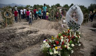 Flowers adorn the fresh grave of slain 18-year-old Antonio Sanchez Valencia as mourners bury another victim from the same shooting in Apatzingan, Michoacan state, Mexico, Thursday, Jan. 8, 2015. (AP Photo/Rebecca Blackwell) ** FILE **