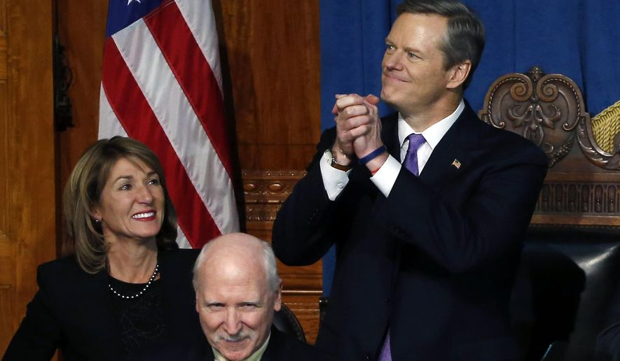 Massachusetts Gov. Charlie Baker and Lt. Gov. Karen Polito acknowledge applause as they are introduced in the House Chamber prior to being sworn in at the Statehouse in Boston, Thursday, Jan. 8, 2015. (AP Photo/Elise Amendola)