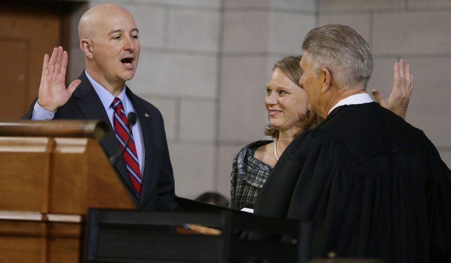 Omaha businessman Pete Ricketts is sworn into office by Nebraska Chief Justice Mike Heavican, right, as Nebraska's 40th governor as his wife Suzanne Ricketts watches, at a ceremony in the Capitol's legislative chamber, in Lincoln, Neb., Thursday, Jan. 8, 2015. (AP Photo/Nati Harnik)