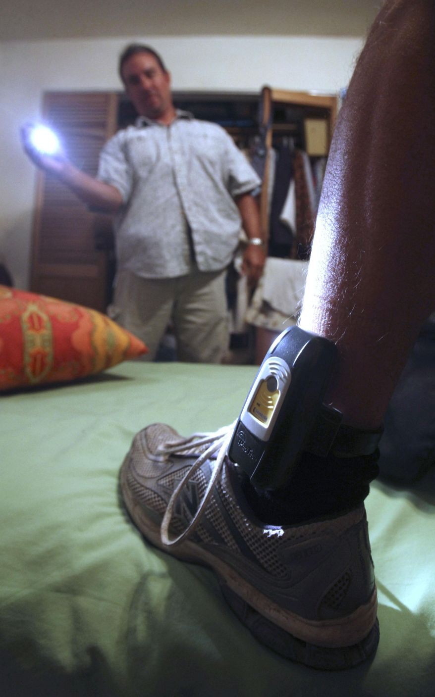 Parole Agent Steve Nakamura uses a flashlight to inspect a GPS locator worn on the ankle of a sex-offender parolee in Rio Linda, Calif., on Aug. 3, 2009. (Associated Press) **FILE**